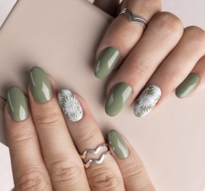 Beautiful womans hands with spring summer floral nail design. Trendy green color manicure close-up