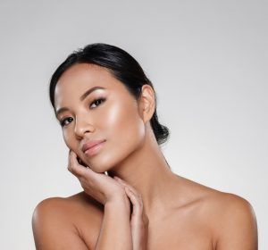 Attractive half-naked asian lady touching her clear skin and looking camera idolsted over grey